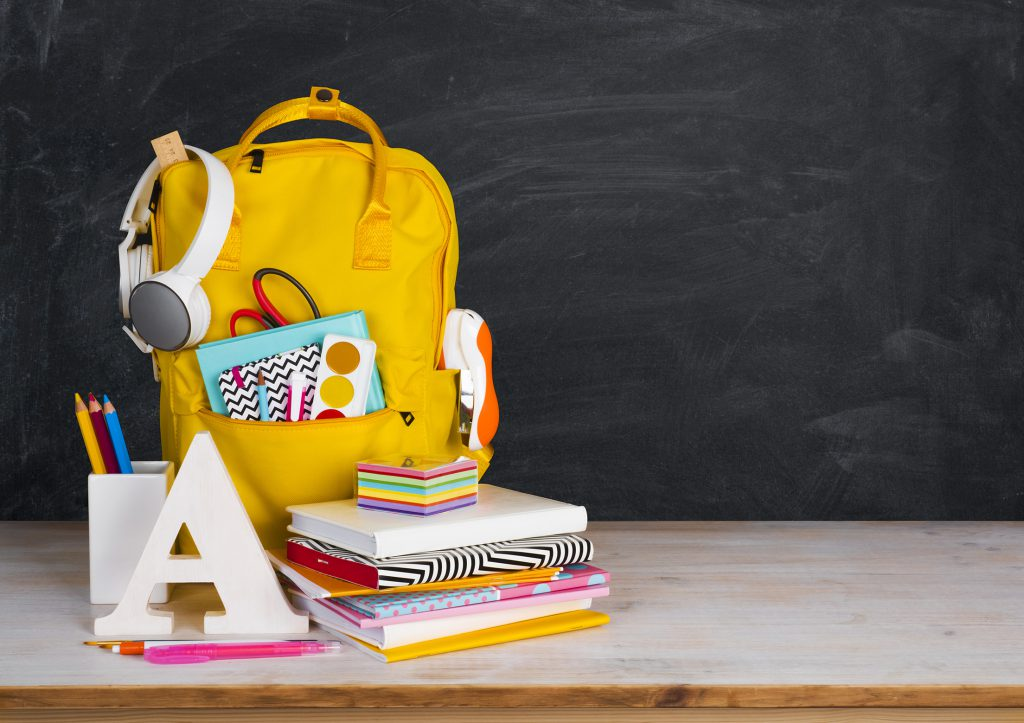 Back to school concept. Educational supplies on table before blackboard